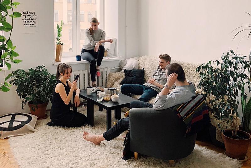 Freunde versammeln sich im Haus, sitzen um Kaffeetisch