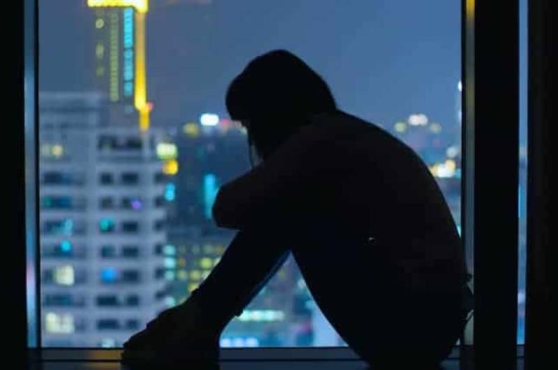 Im Dunkeln am Fenster sitzt eine Frau