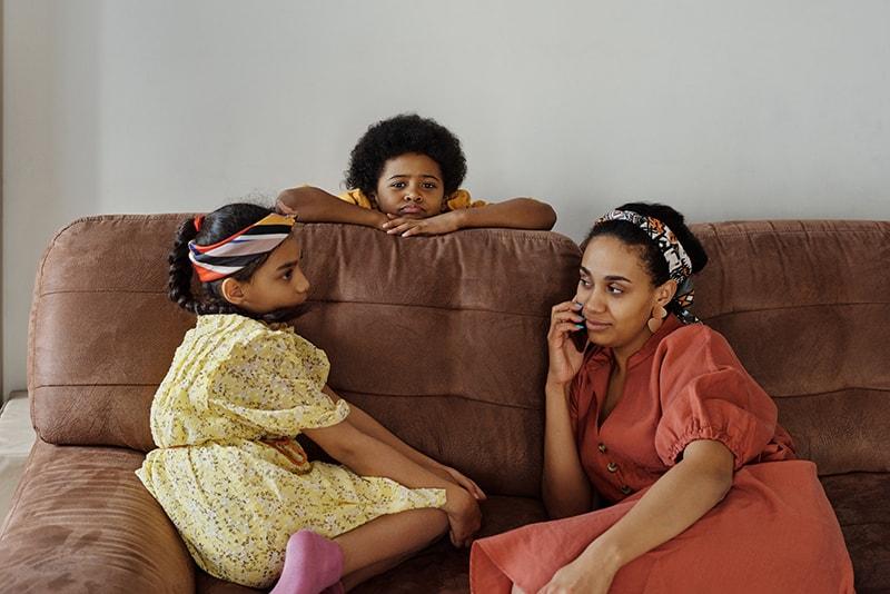 Kinder und eine Mutter sitzen auf dem Sofa, während die Mutter telefoniert