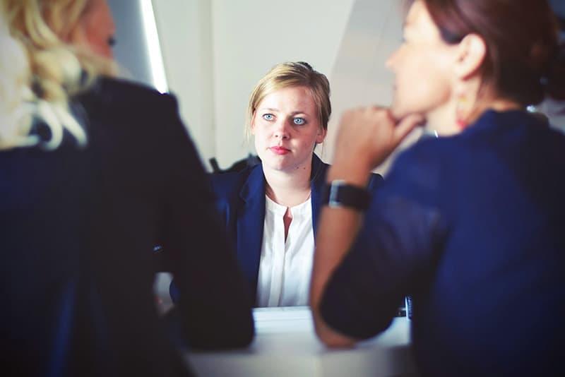 Konkurrenzdenken Frau, die ihre Kollegen beim Geschäftstreffen betrachtet
