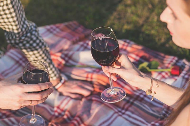Liebespaar, das Wein auf einem Picknick trinkt, während es auf der Decke sitzt