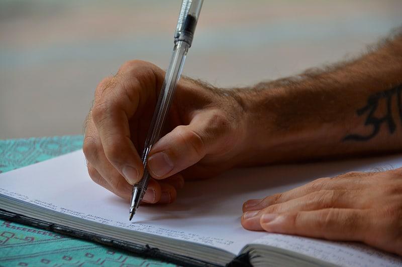 Mann Schreiben in Notizbuch auf blauer Oberfläche