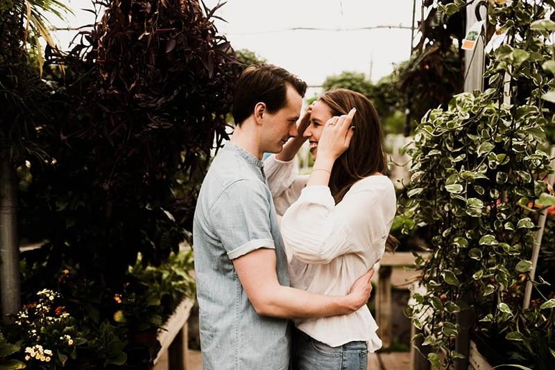 Mann hält Frau um Taille mit Pflanzen umgeben