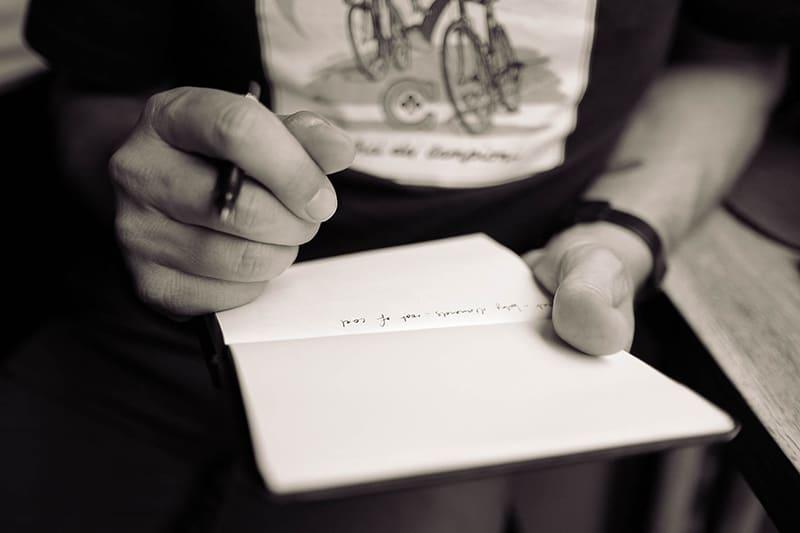 Mann hält Notizbuch und Bleistift