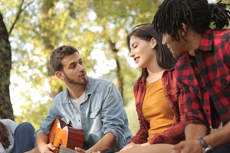 Mann mit Gitarre, die zu Freunden singt, während er Mädchen ansieht
