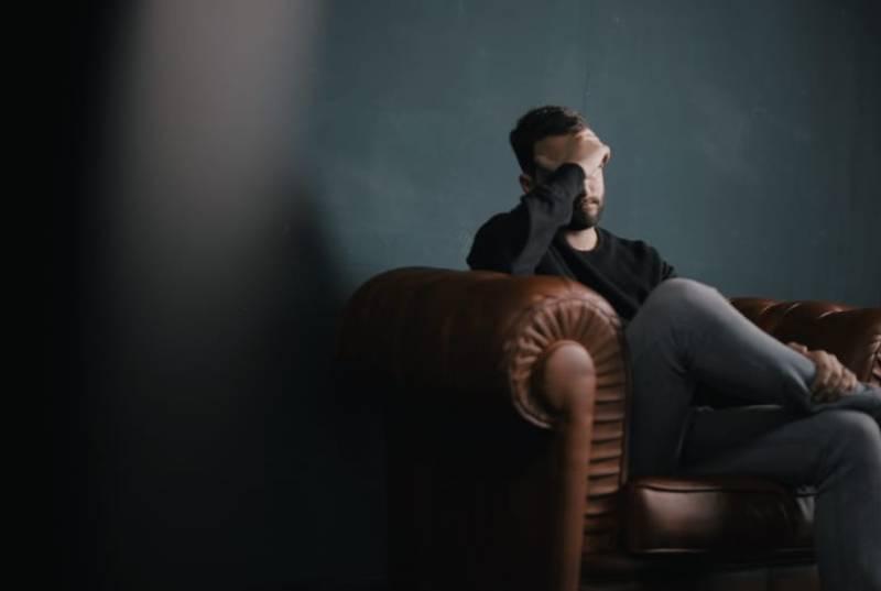 Mann sitzt auf ofa gegen Wand