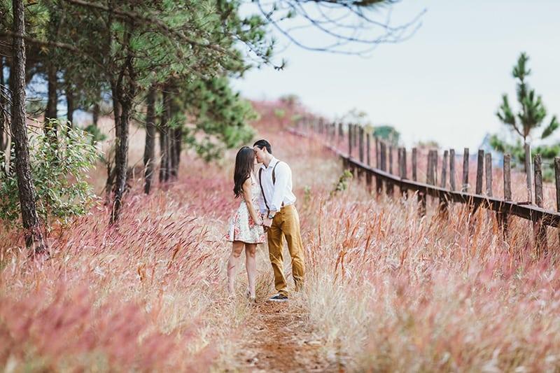 Mann und Frau küssen sich beim Händchenhalten auf dem Feld