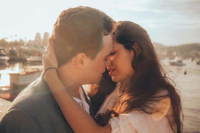 Mann und Frau küssen sich neben der Bucht Während der Tageszeit