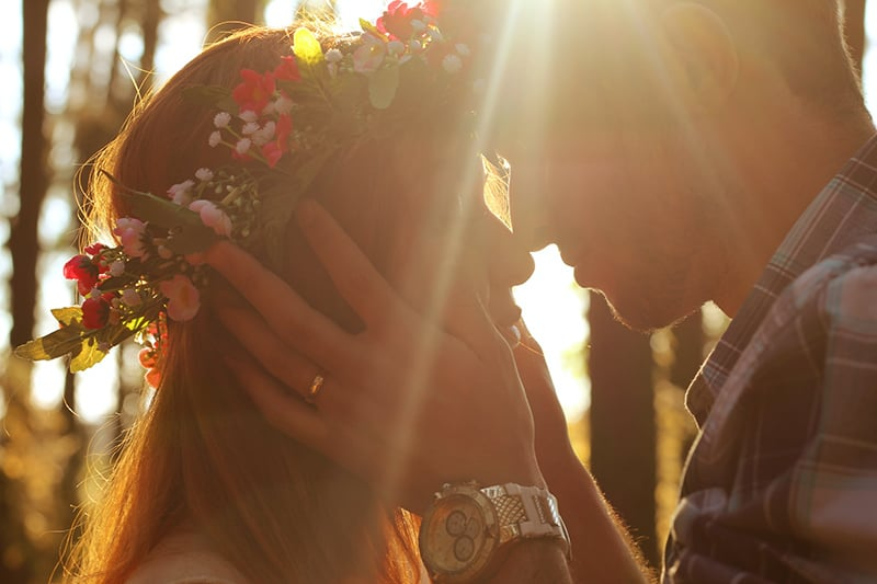 Mann und Frau küssen sich während des Sonnenuntergangs
