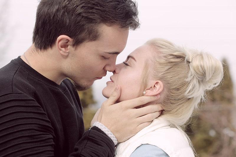 Mann und Frau kurz davor zu küssen während des Stehens