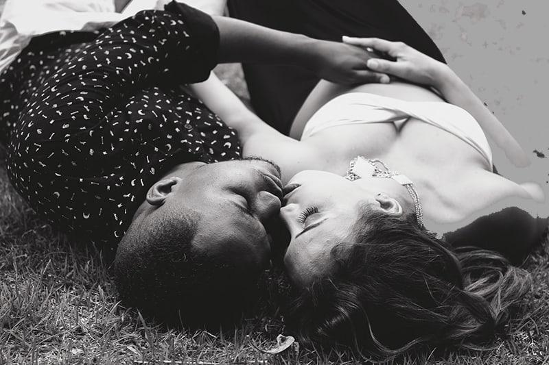 Mann und Frau liegen im Gras beim Kuscheln