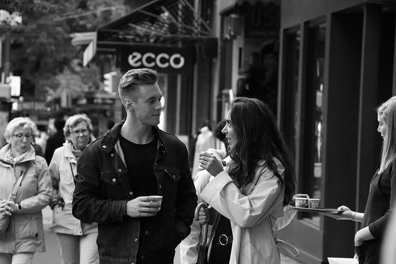 Mann und Frau trinken Kaffee auf dem Bürgersteig