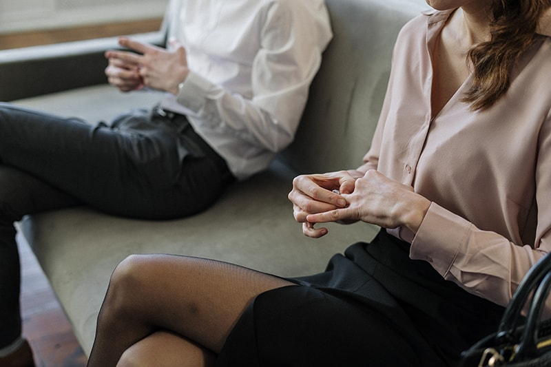 Mann und Frau nehmen ihre Eheringe ab, während sie auf dem Sofa sitzen