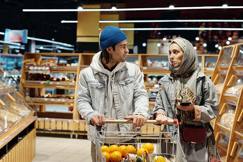 Mann und Frau zusammen im Lebensmitteleinkauf, der neben Regalen steht