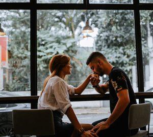Ein Mann küsst die Hand einer Frau, während er am Fenster sitzt