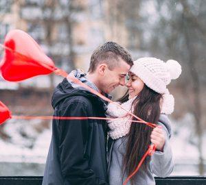 eine Frau, die Luftballons hält, um einen Mann zu küssen