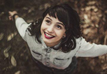 lächelnde Frau, die nach oben schaut und Arme in der Natur ausbreitet
