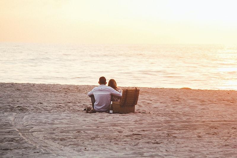 Paar auf einem Picknick am Wasser beobachten Sonnenuntergang
