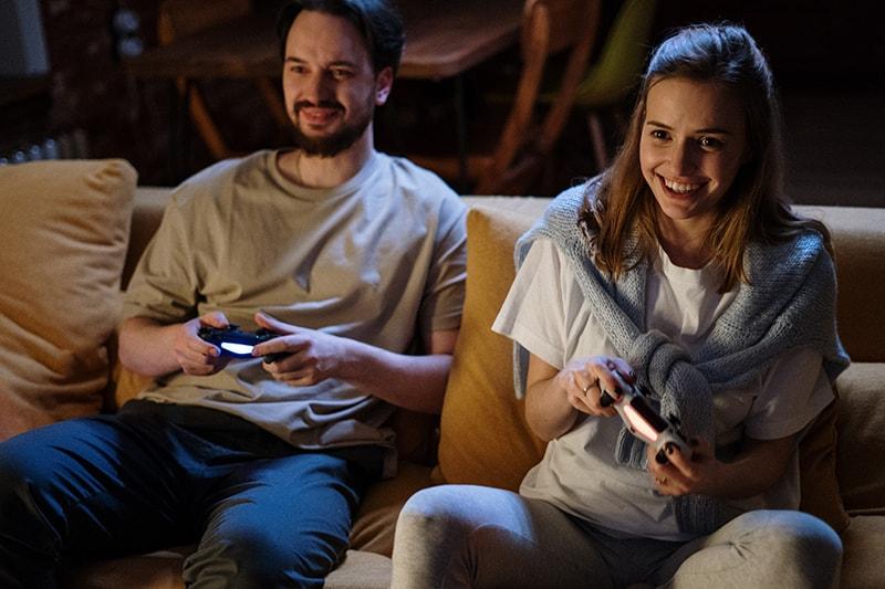 Paar, das zusammen ein Videospiel spielt, während es auf der Couch sitzt