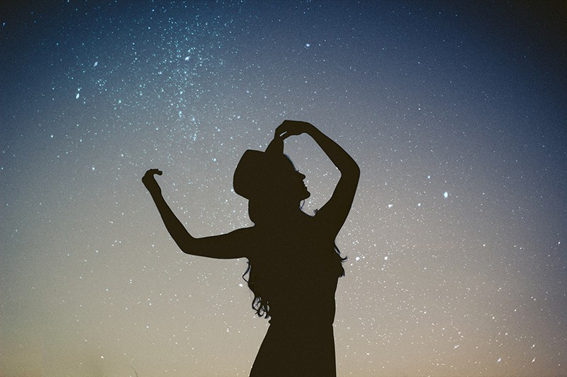 Silhouette einer Frau unter Sternenhimmel