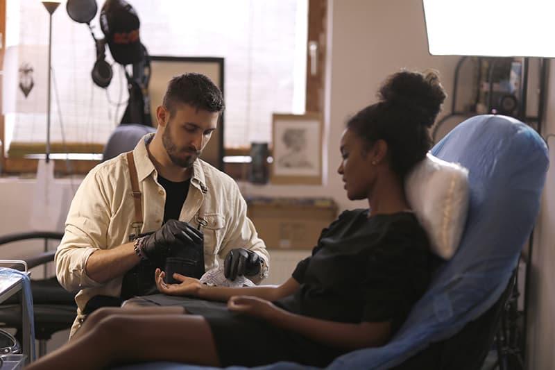 Tätowierer sitzt neben Frau im schwarzen Kleid