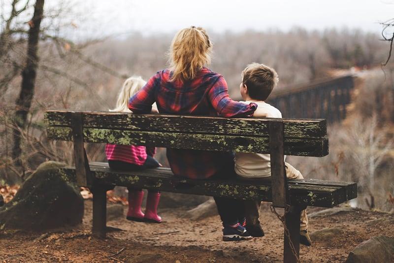 eine Mutter und zwei Kinder sitzen auf der Bank in der Natur
