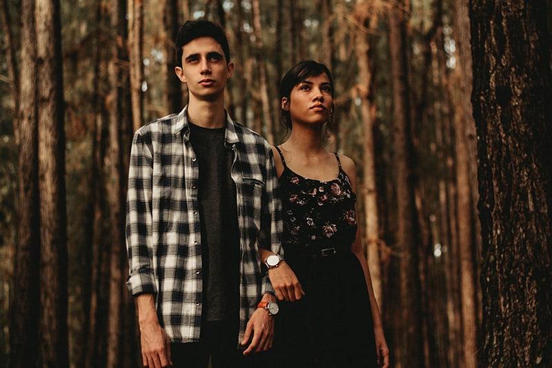 Ein ernster Mann und eine ernsthafte Frau stehen im Wald und halten sich an den Händen