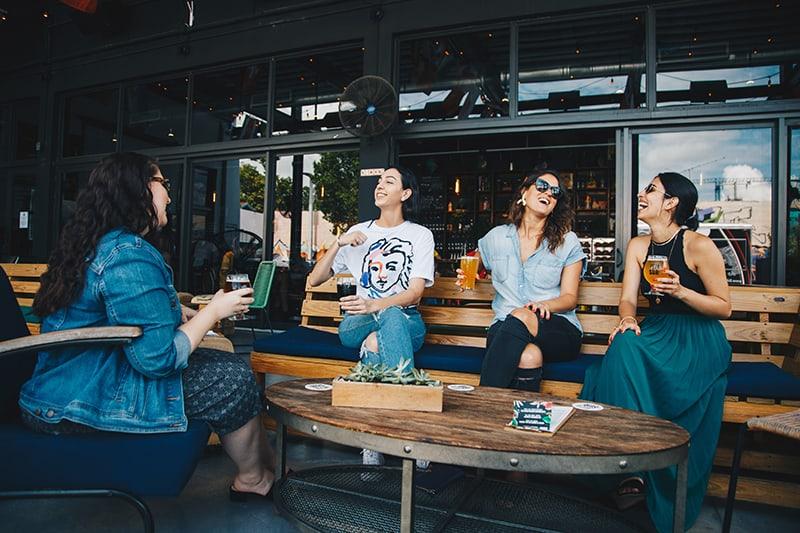 Vier Frauen unterhalten sich, während sie auf der Bank im Café sitzen