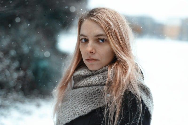 blonde Frau im Schnee mit einem Schal