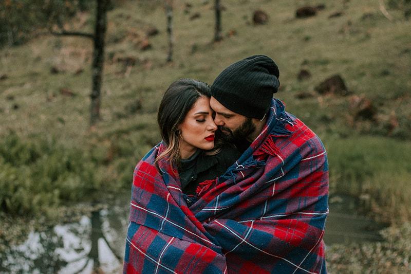 das Paar mit Decke bedeckt im Freien stehen