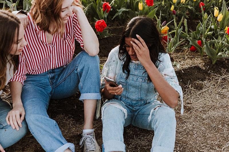 drei Freundinnen hängen rum während auf dem Boden sitzen