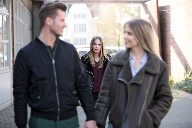 eifersüchtige Frau, die hinter lächelndem Paar geht, das Hände hält