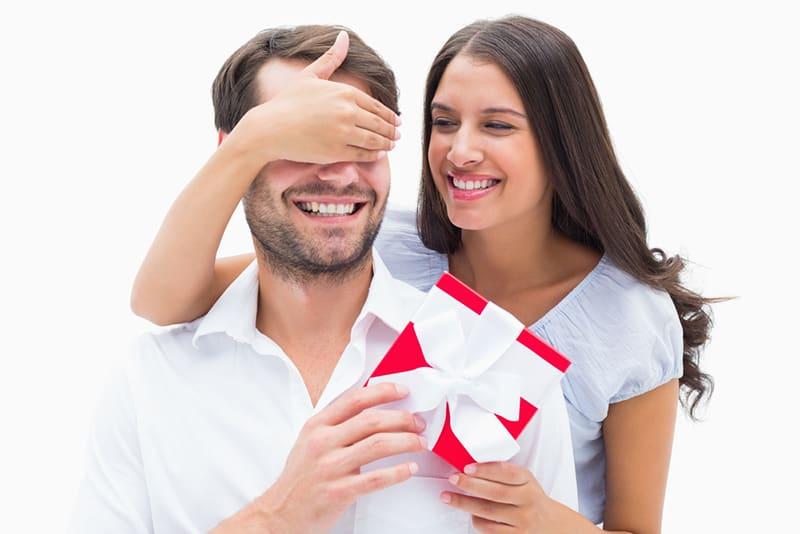 ein Mädchen, das einen Freund mit einem Geschenk zum Jubiläum überrascht