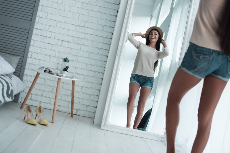 ein Mädchen in kurzen Hosen posiert vor einem Spiegel