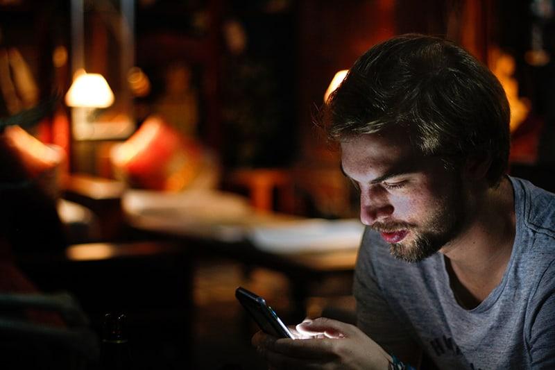 Ein Mann liest eine Nachricht auf einem Smartphone und sitzt in der Dunkelkammer
