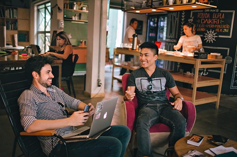 Ein Mann benutzt einen Laptop, der mit einem Freund sitzt, während er sich unterhält