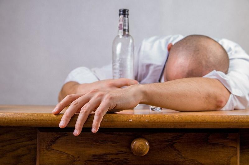 Ein Mann mit einem Kater von Alkohol, der sich an die Bar lehnt