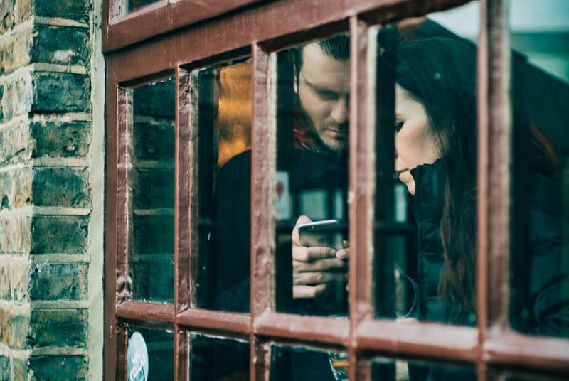 Ein Mann benutzt ein Smartphone neben einer Frau, während er in der Nähe des Fensters steht