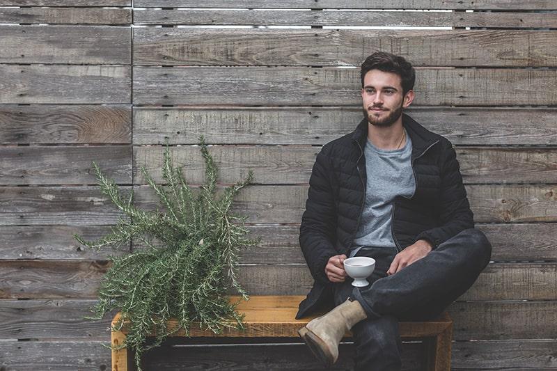 Ein Mann sitzt auf der Bank neben der Pflanze