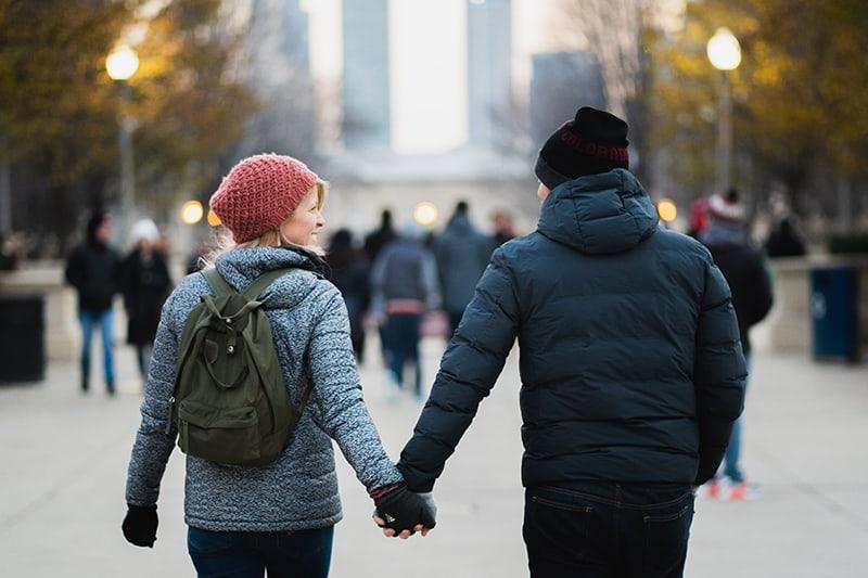 Ein Mann und eine Frau halten sich beim Gehen auf der Promenade an den Händen