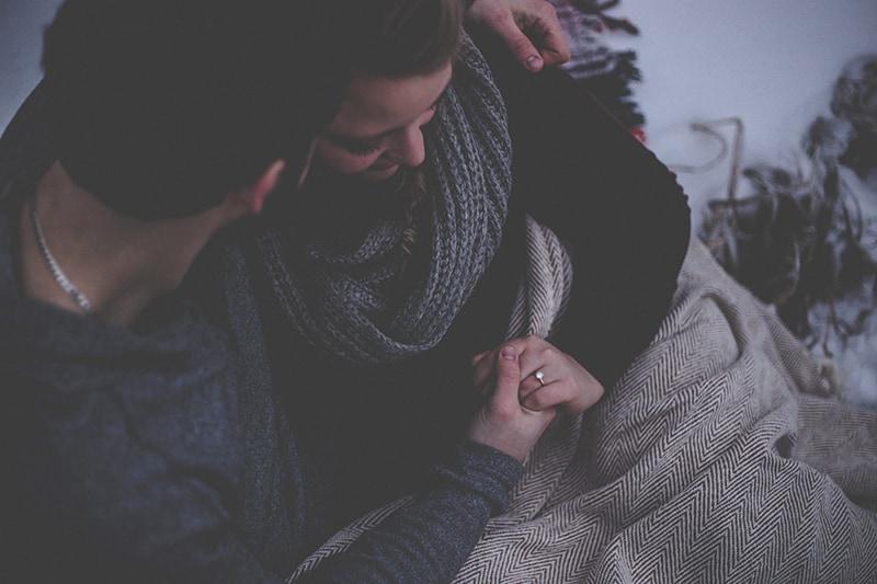ein Mann und eine Frau, die Hände halten, während sie mit Decke bedeckt sitzen