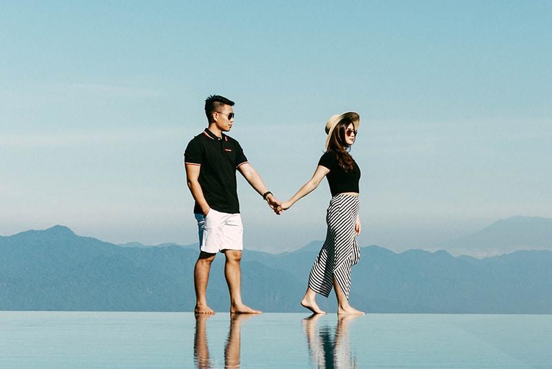 ein Mann und eine Frau, die Hände halten, während sie am Rand des Schwimmbades stehen