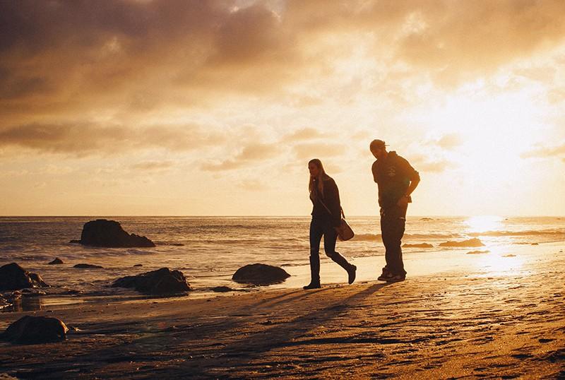 ein Mann und eine Frau, die an der Küste spazieren geht beim Sprechen