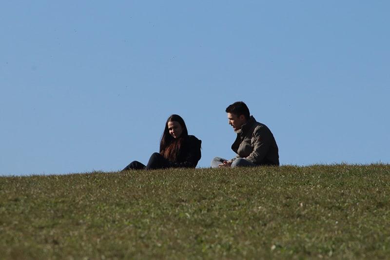Ein Paar, das ein ehrliches Gespräch führt und im Gras sitzt