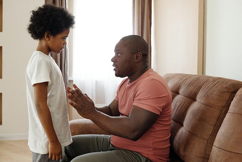 Ein Vater spricht mit seinem Sohn, während er auf dem Sofa sitzt