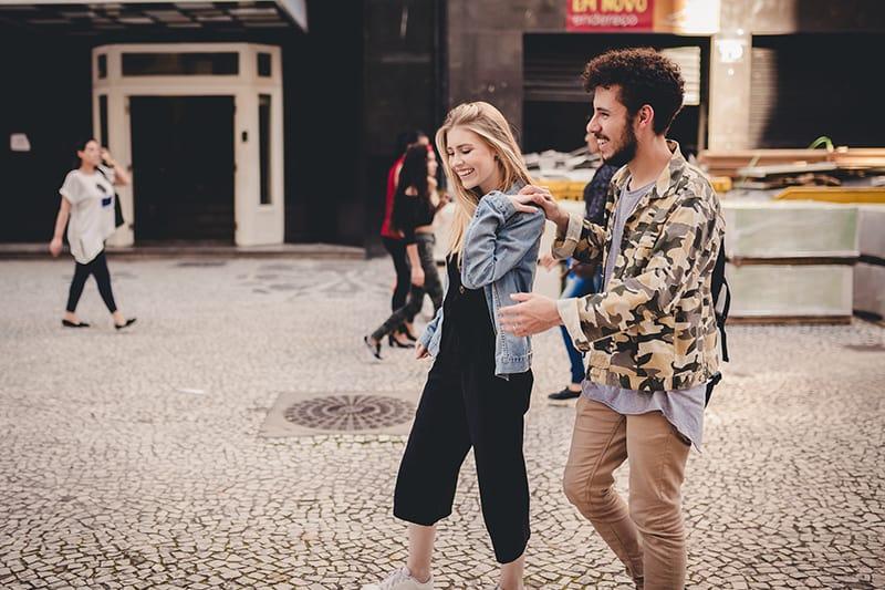 ein glückliches Paar, das zusammen in der Stadt spazieren geht