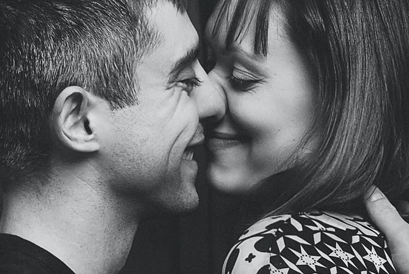 Ein lächelnder Mann will eine Frau küssen, während er sie umarmt