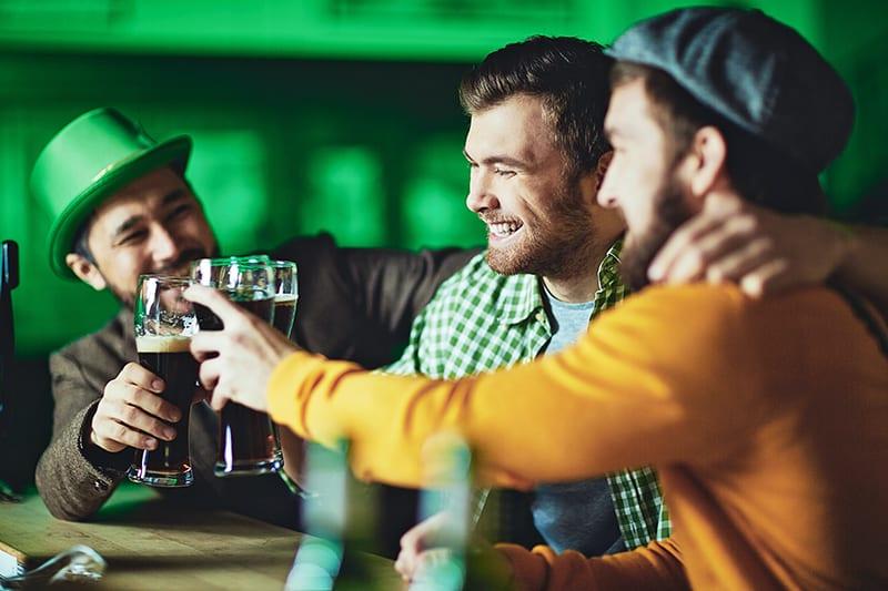 ein lächelnder Mann, der mit Freunden in der Kneipe etwas trinkt