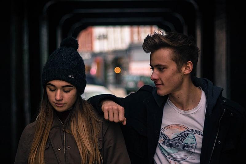 ein lächelnder Mann, der sich auf eine ernste Frau stützt, während er in der Stadt steht