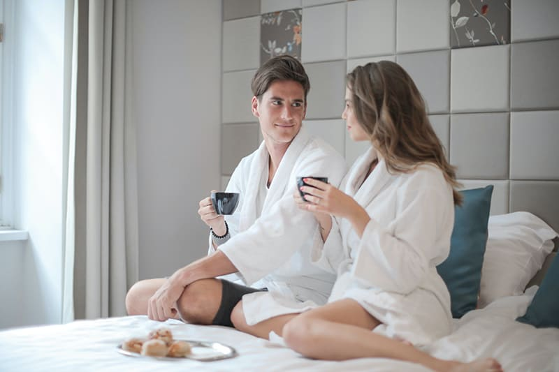 Ein liebevolles Paar, das einen Bademantel trägt, während es im Bett sitzt und frühstückt